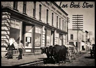 Picture of original building circa early 1900's. Two people walking on sidewalk and ox driven cart sitting on the street out front of the builing.